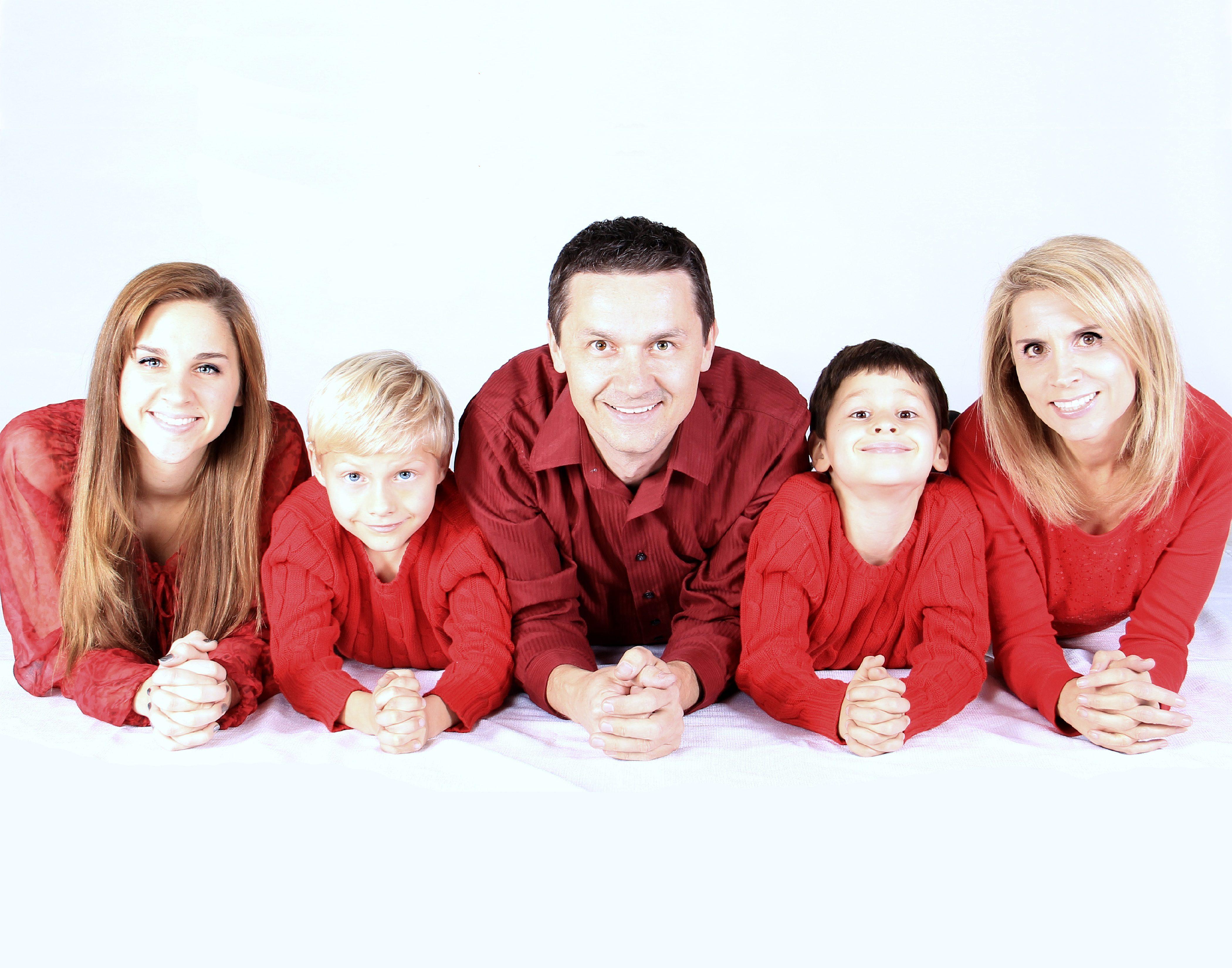 Familie liegend nach vorne mit roten Kleidern
